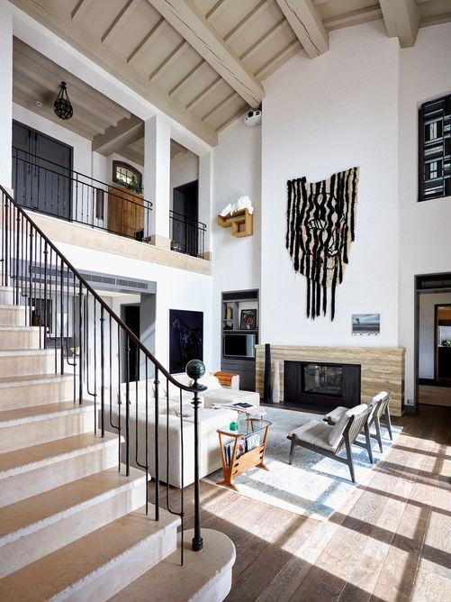 Au cœur de la villa, le salon offre un volume généreux et une hauteur sous plafond de 6,5mètres. Canapé WALL de Living Divani. Porte-journal et paire de fauteuils vintage achetés dans une foire aux antiquités à Londres. Tapis KNOTS ABSTRACT de Knots Rugs. Au-dessus de la cheminée SAPHIR de Rüegg, peinture laineuse grand format «Klowl» de Caroline Achaintre.