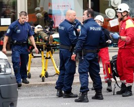 Policiais em torno de uma pessoa ferida na maca (Foto: G1)