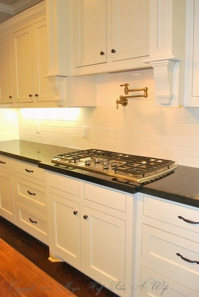Traditional white kitchen stove area with water spout