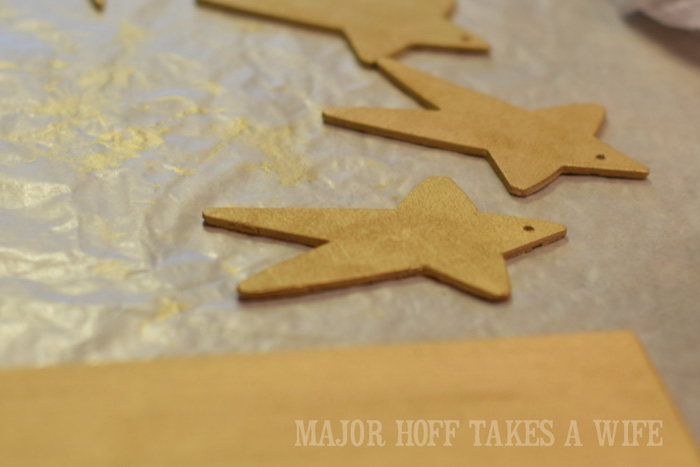 Painting Christmas ornament stars with Metallic paint. Looking for homemade Christmas gifts? Look no further than these homemade Christmas ornaments. Use them as tree decorations, to grace your holiday table, or for fun tags to gifts! The ideas and endless and your friends and family will love these glittery stars personalized just for them!