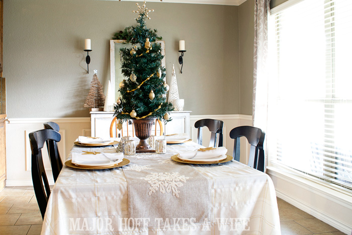 Use a table top tree to make a simple centerpiece. A delightful Dining Room Holiday Tour. See how Mrs Major Hoff decorates for Christmas. The tour features table decorations, dining room decorating ideas, place settings and an idea for  homemade Christmas gift that can be personalized for your holiday guests. This post is part of the Home For The Holidays Blog Tour.
