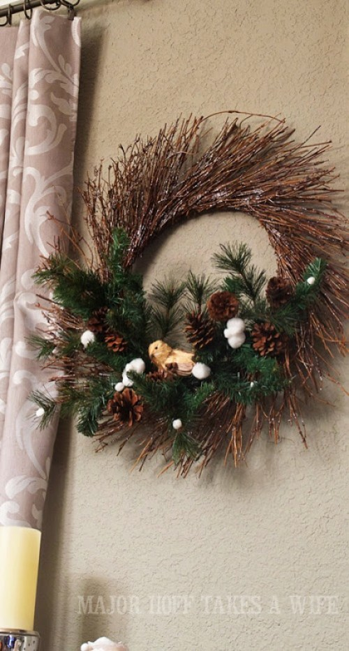 World Market winter wreath knock off. World Market inspired wreath. A fun twist on a Christmas wreath. Make a winter wreath that will last all season long and well past. This cute grapevine wreath is adorned with a tiny bird, pinecones, greenery and pom poms. You won't believe how cheap and easy this was to make! And so simple! #Christmas #winter #holiday #wreath #nature #knockoff