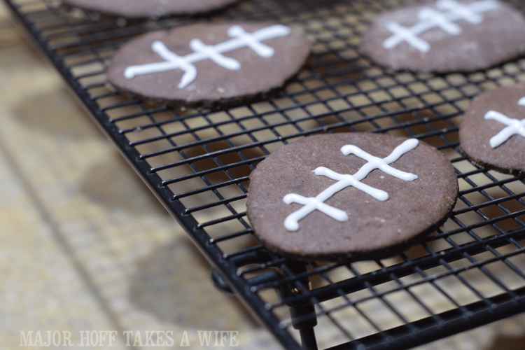 Iced football cookies. Looking for a fun party for your teenage boy? Why not throw a Football video game party? Easy ideas for how to entertain kiddos during the Big Game. Features DiGiorno pizza, personalized football cups, free printable lanyards, and an incredible recipe for football shaped ice cream sandwiches! #GameTimeMVP #CollectiveBias #ad