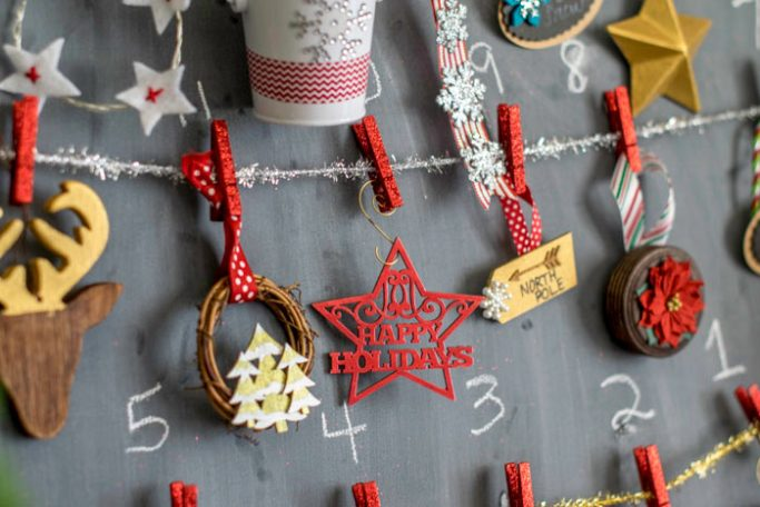Small ornaments on a chalkboard for a DIY advent calendar craft