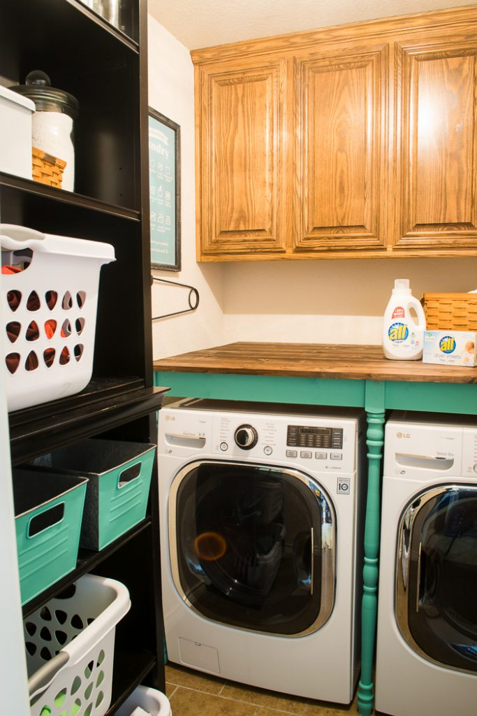 bookshelves hold laundry and a diy table in the laundry room helps with organization