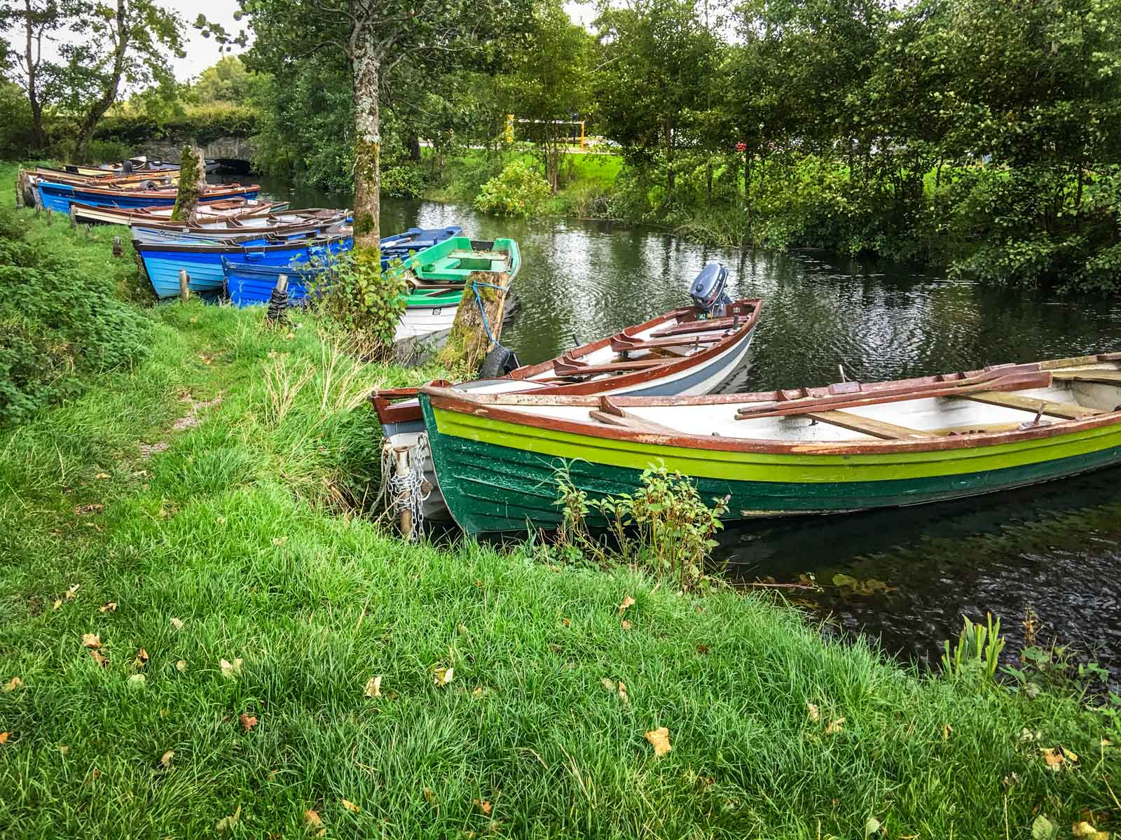 colorful boats next to Ross Castle in Killarney