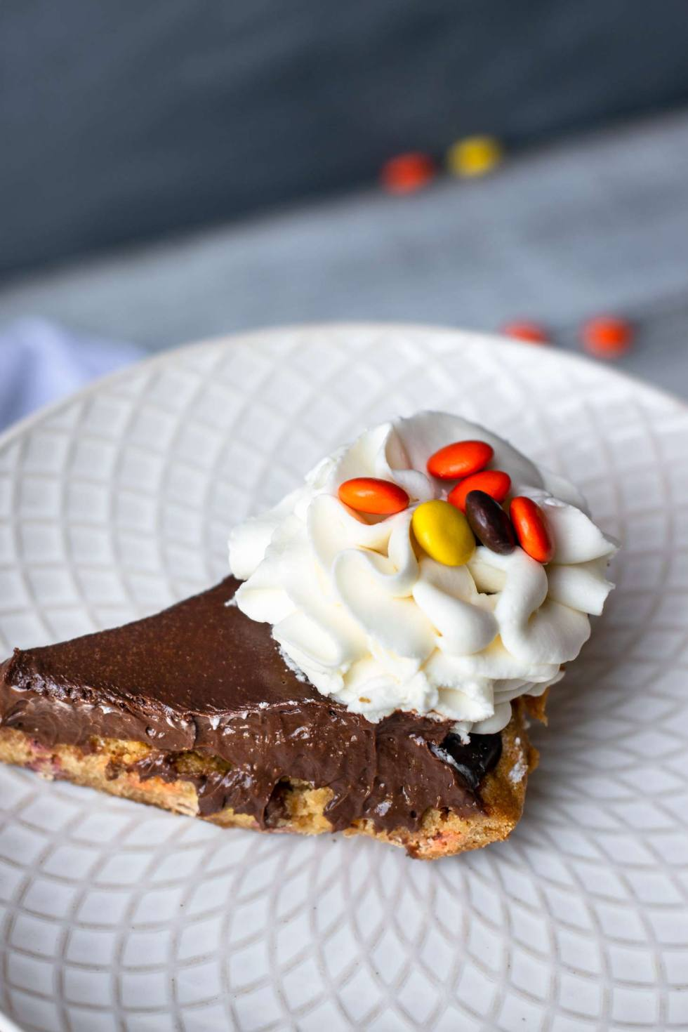 Peanut butter and chocolate pie on a white plate with Reese's pieces.