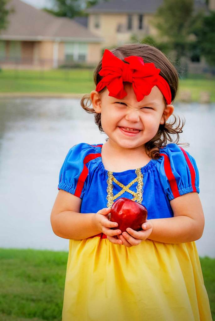 little girl in a Snow White dress up costume with an apple