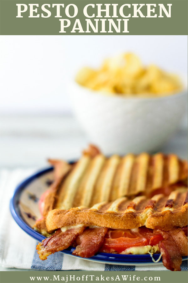 Pesto chicken panini with bacon and tomatoes and a bowl of potato chips