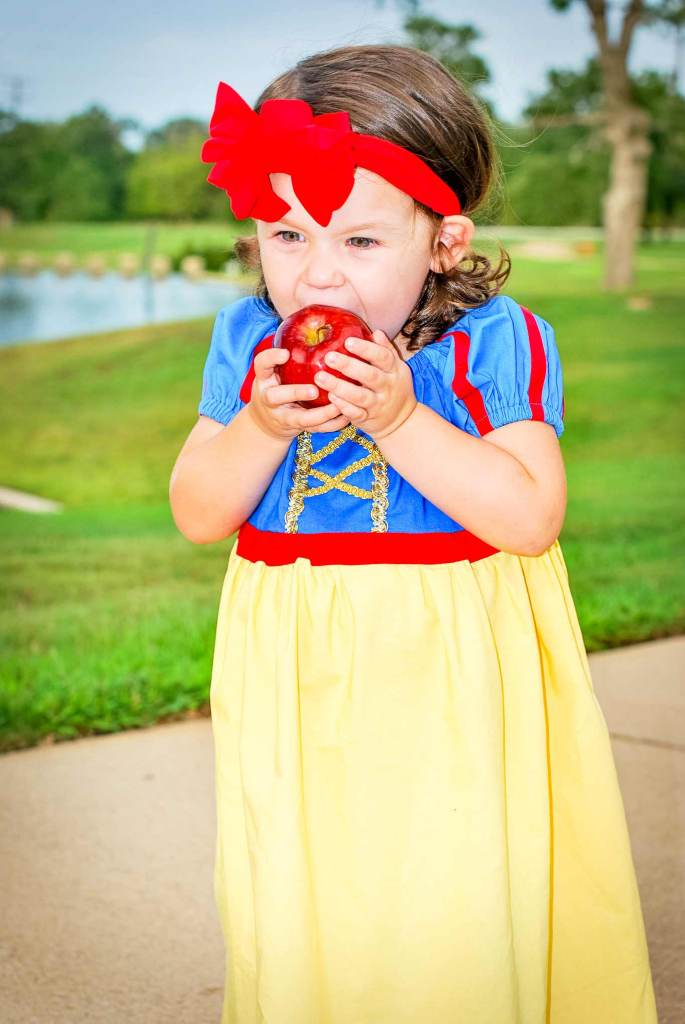 Red stripes on sleeves, gold ribbon on the bodice, and more details make this diy Snow White costume adorable on a toddler