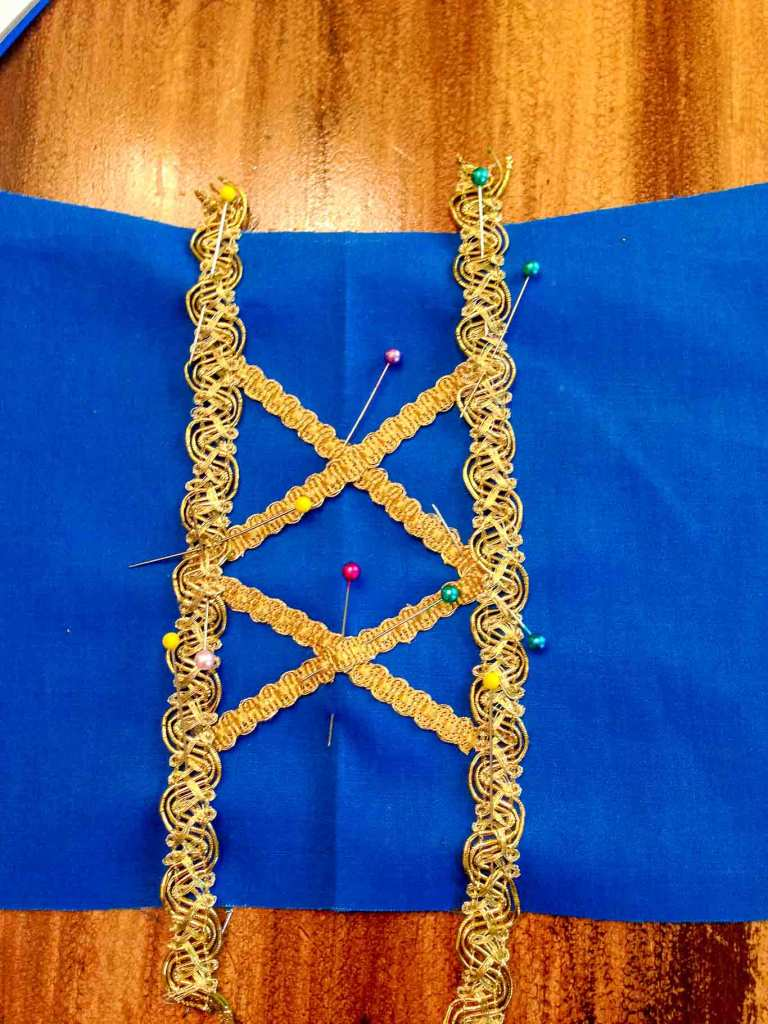 Up close view of gold ribbon detail on Snow White peasant dress bodice before sewing
