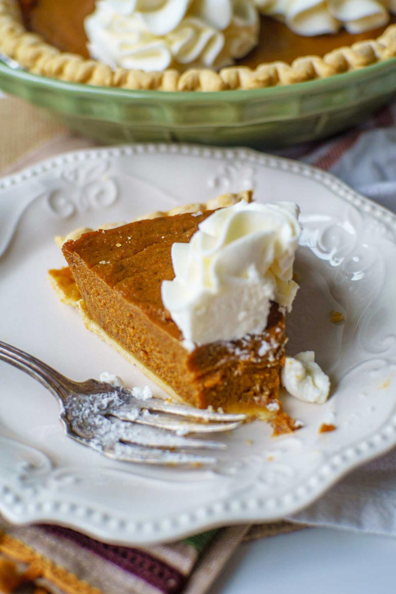 A simple pumpkin molasses pie topped with sturdy whipped cream frosting flowers
