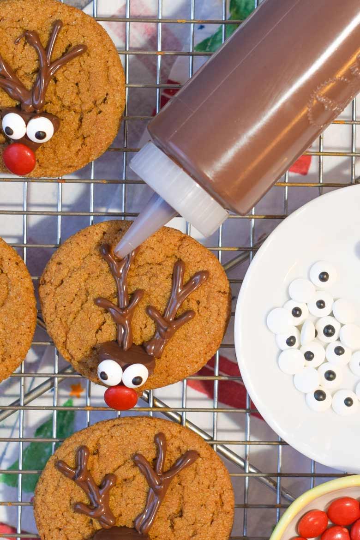 Piping chocolate antlers on to gingerbread reindeer cookies