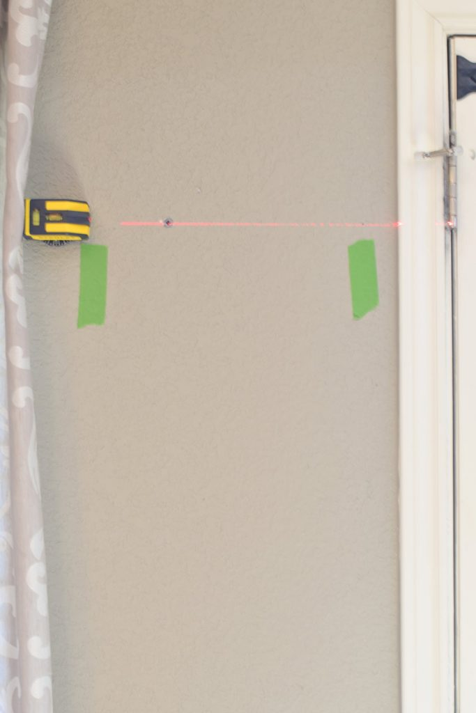 Using a laser level to hang a shelf while also finding available studs and using wall anchors where missing