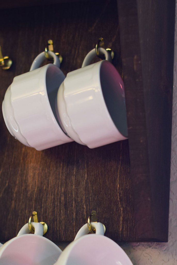 Cup hooks are screwed into this kitchen wall shelf for an easy DIY wall mug rack
