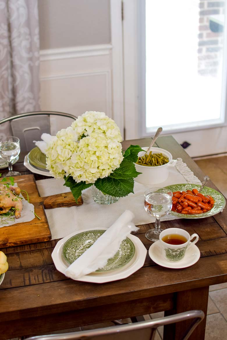white hydrangeas with green leaves on a table to accent green ironstone dishes and side dishes of green beans, bbq smokies and Cornish hens