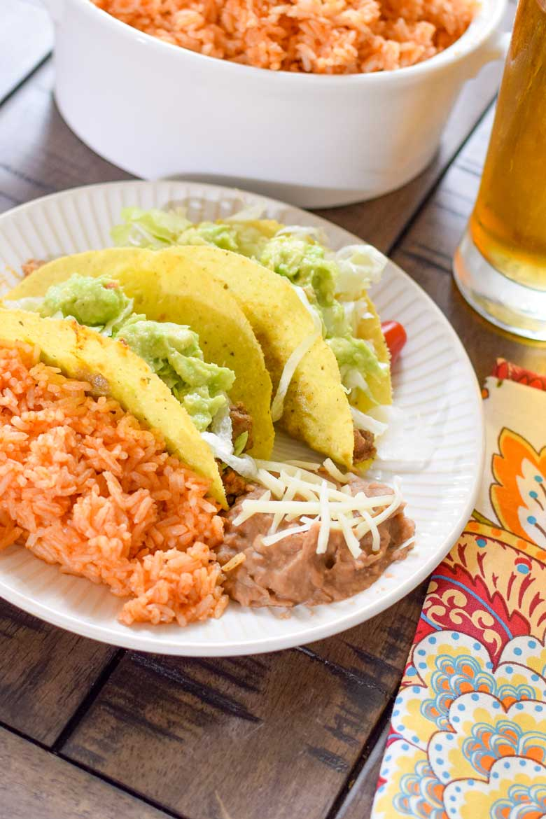 Instant pot Mexican rice on a plate with refried beans and corn shell tacos