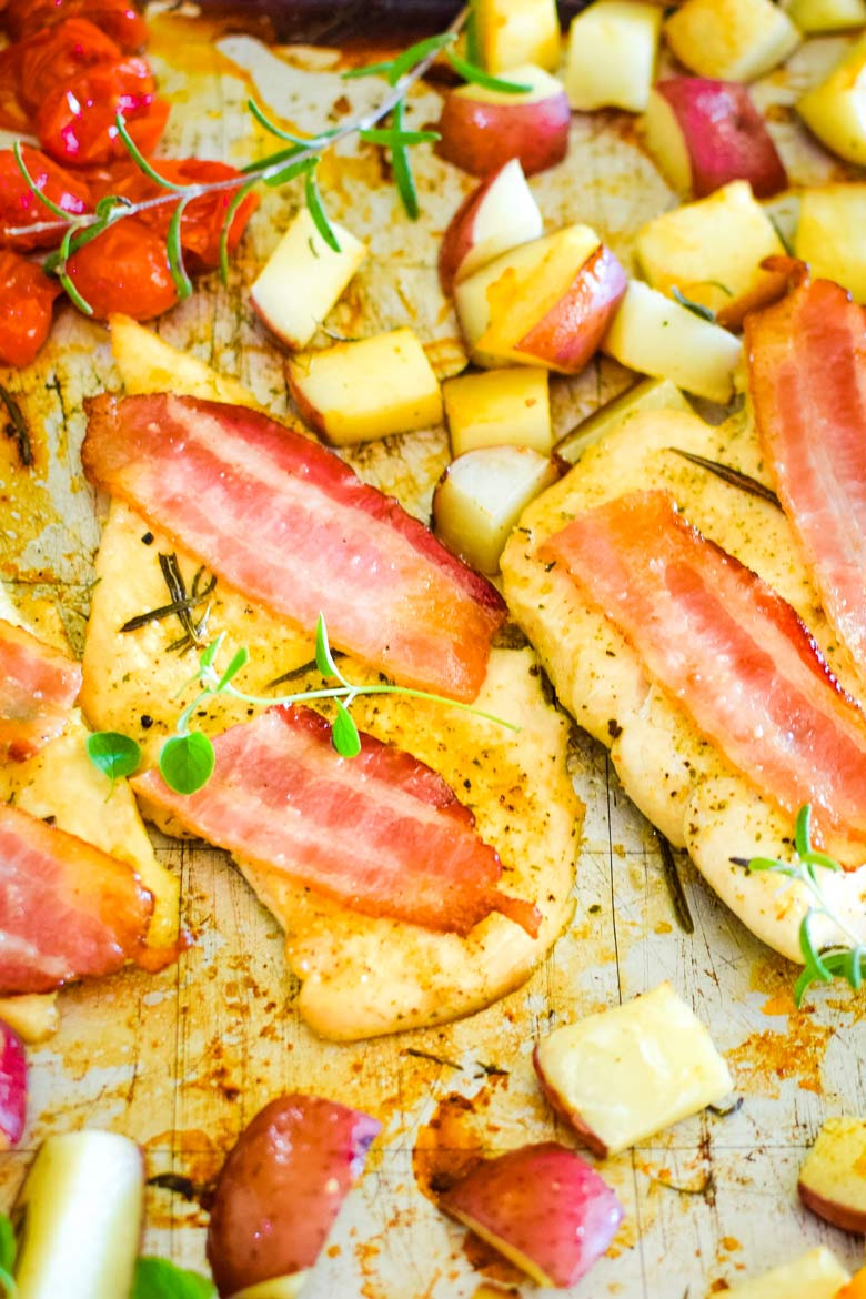 boneless skinless chicken breasts baked with herbs and bacon alongside vegetables