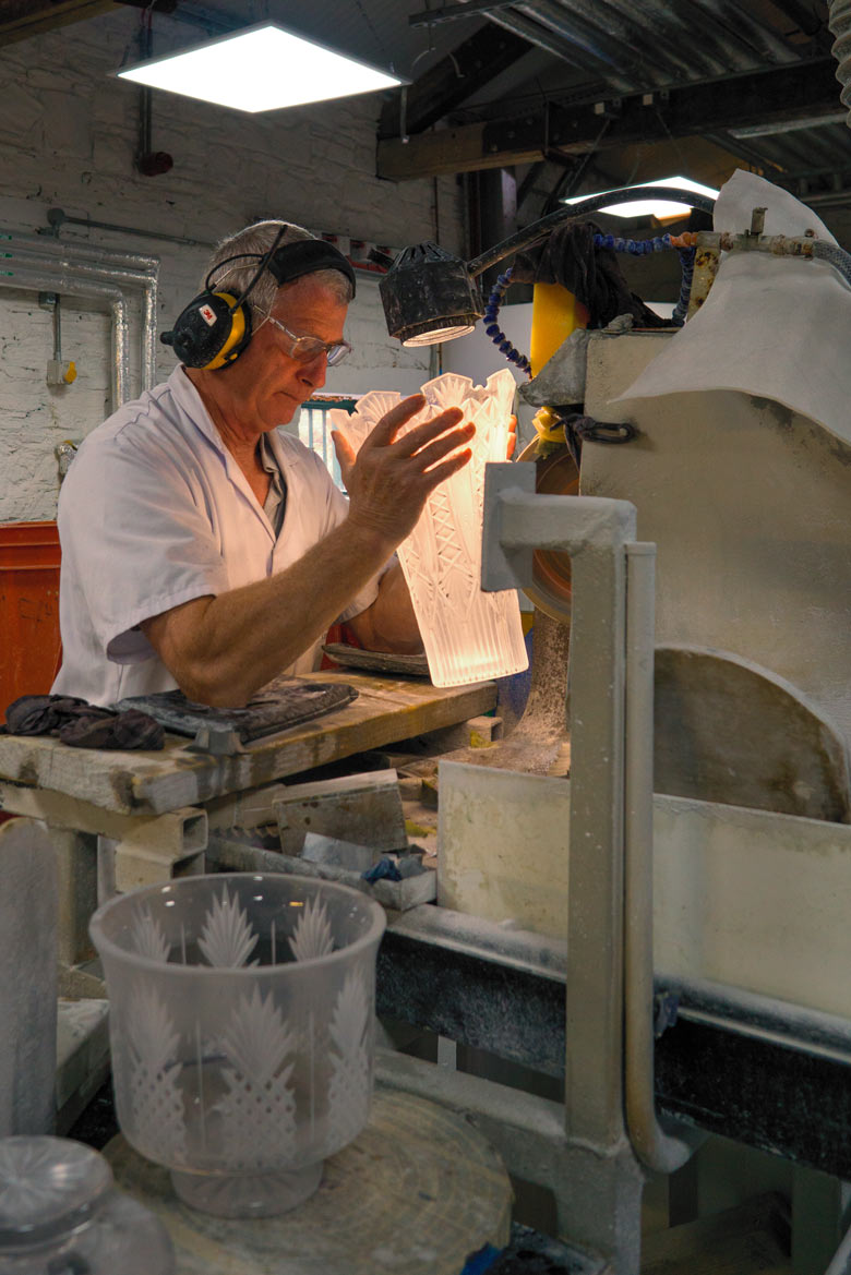 cutting a piece of crystal on a diamond blade on the factory floor in Ireland