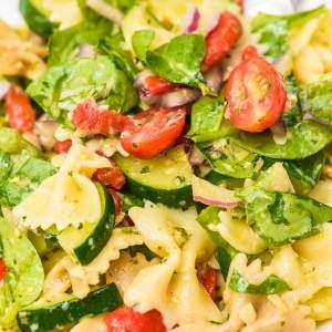 cold pasta salad with artichoke pesto sauce, zucchini, spinach, tomatoes and fresh summer veggies