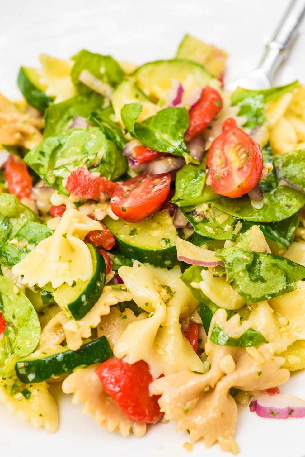 cold pasta salad with artichoke pesto sauce, zucchini, spinach, tomatoes and fresh summer veggies