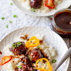 spicy meatballs peppers and rice on a white plate