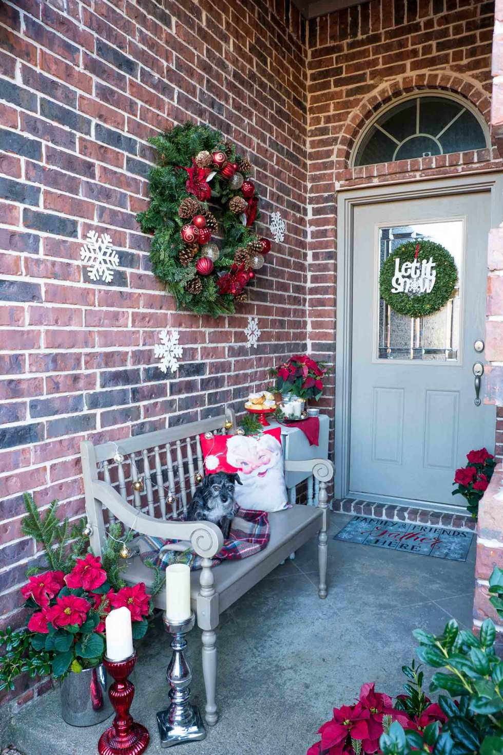 Christmas decor on front porch with a dog on a bench