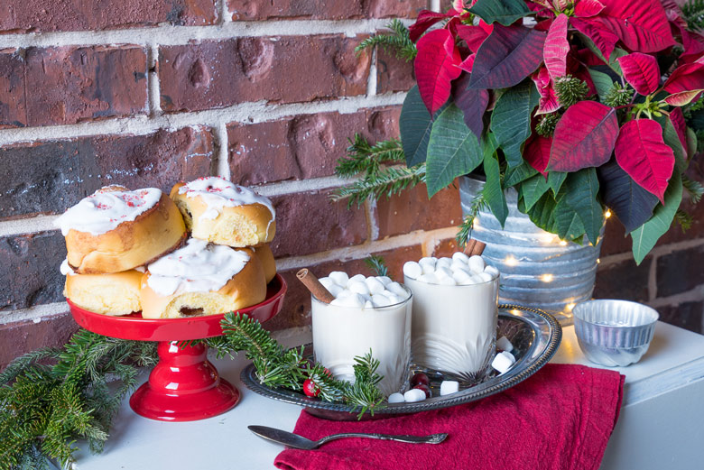 white cocoa on a table with cinnamon rolls and a poinsetta