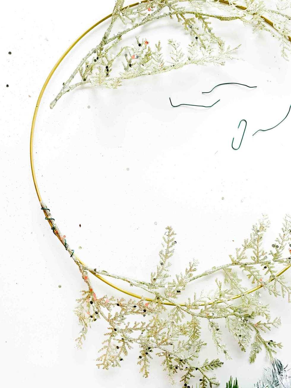 wiring a floral stem onto a metal wreath hoop