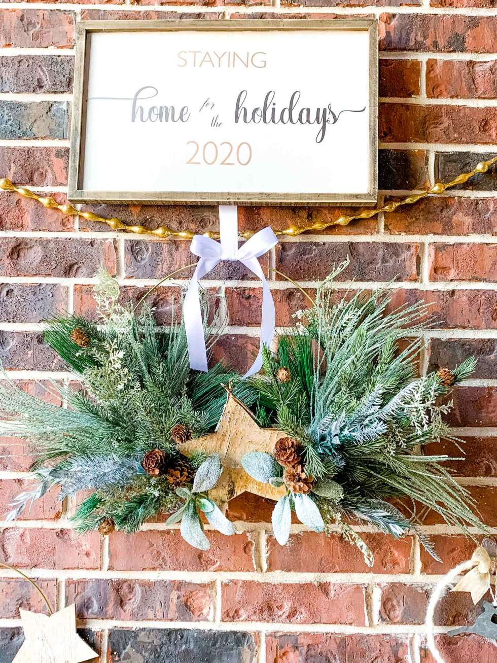 wooden Christmas sign above gold garland and a wreath with greenery