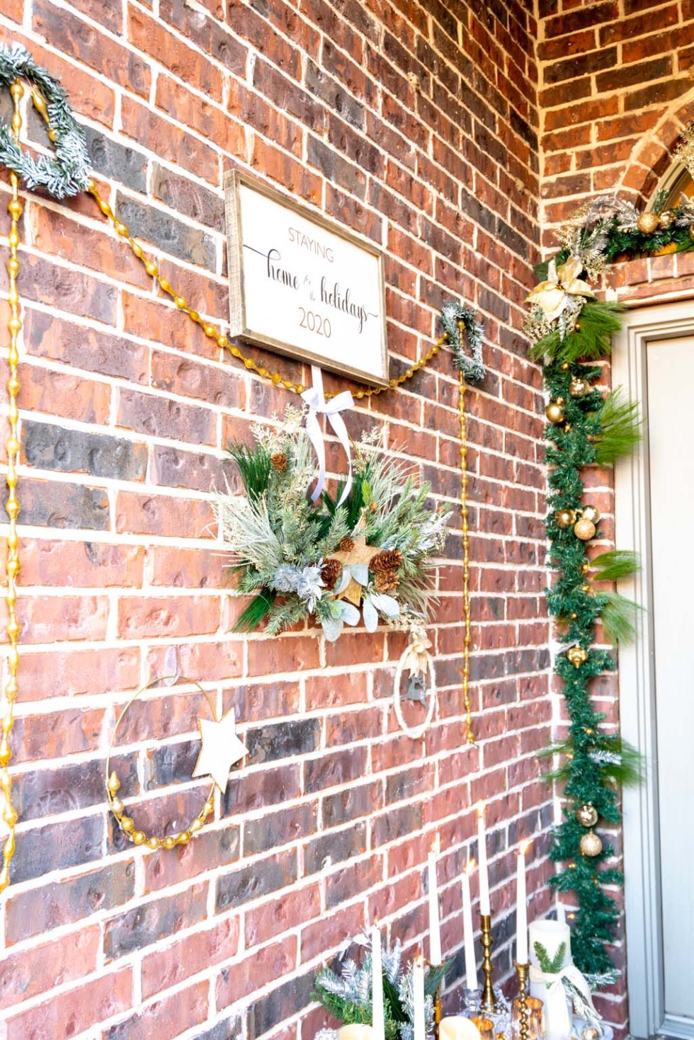 a wall of wreaths and a home for the holidays sign