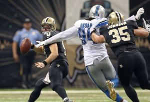 Dec 21, 2015; New Orleans, LA, USA; New Orleans Saints quarterback Drew Brees (9) runs from a tackle attempt by Detroit Lions defensive end Ezekiel Ansah (94) while Saints fullback Austin Johnson (35) blocks in the second quarter of the game at the Mercedes-Benz Superdome. Mandatory Credit: Chuck Cook-USA TODAY Sports