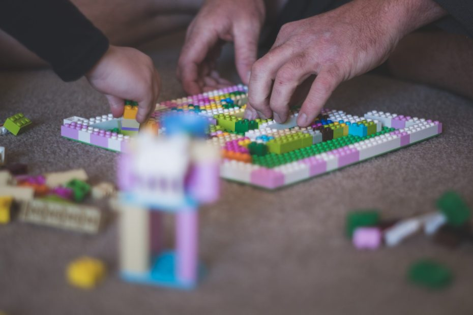 Grandfather and grandchild playing with Legos
