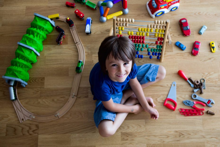 Young boy playing with toys in room