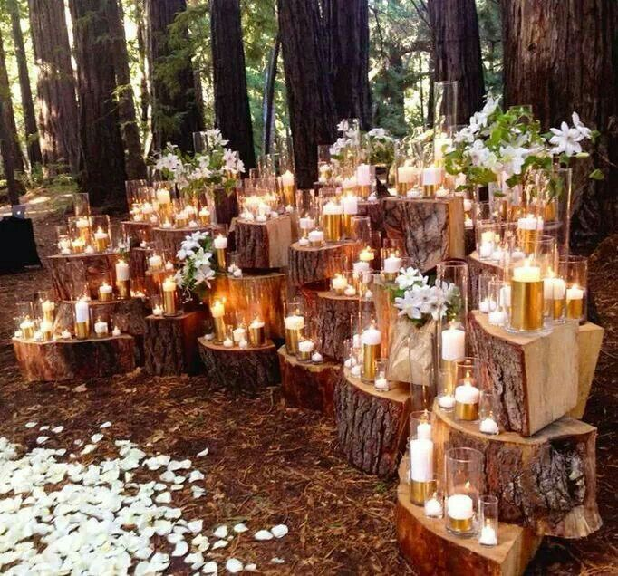 Chunks of tree trunks stacked with candles and flowers on it