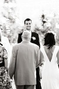 Groom smiling at bride walking down aisle