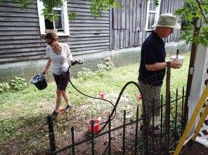 Day 5: Jennifer washes buckets while Edward paints.