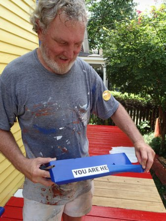 """Day 5: Greg takes the tape off of the mailbox revealing the """"You are Here"""" bumper sticker."""