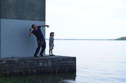Gabe watches his dad throw a rock into the Wando River.