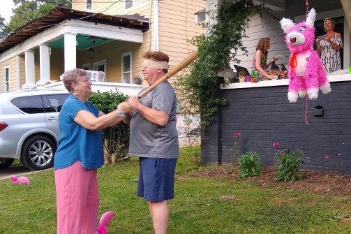 Dian (the birthday girl) prepares Patrick to take a swing at the piñata.