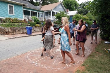 Neighbors participate in a cakewalk on the sidewalk in Cabbagetown Park.
