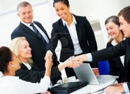 men and women shaking hand oner a laptop