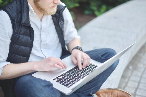 a man typing on s laptop
