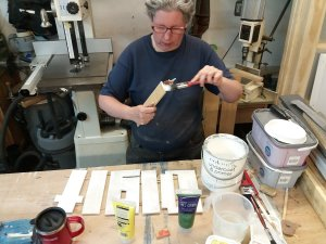Sue paints the letter cut outs with primer