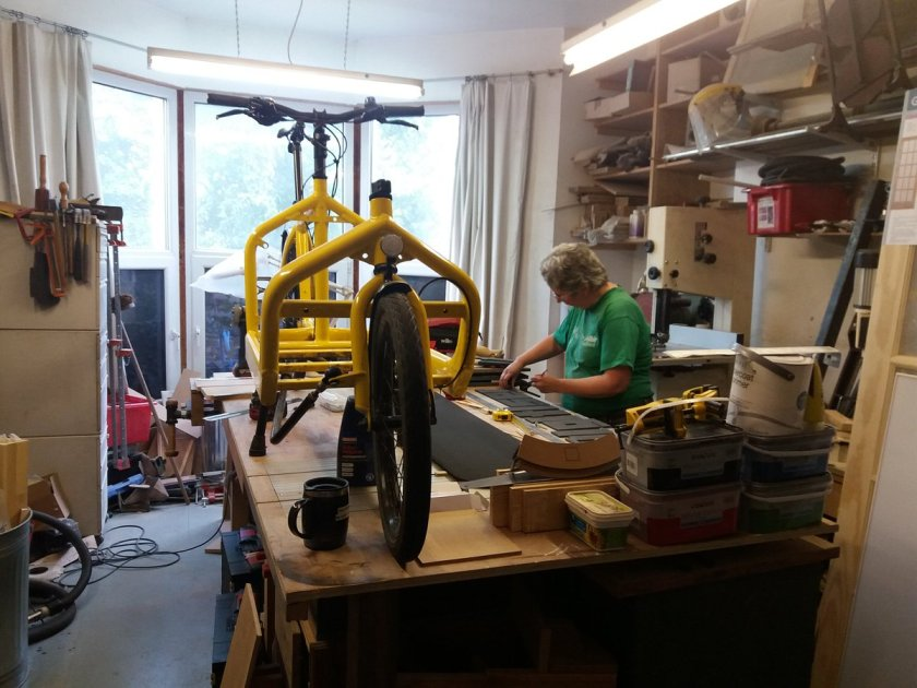 Sue working at the bench, with a cargo bike also on the bench top
