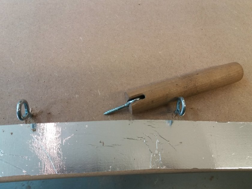 a piece of dowel with a slot cut in it to turn screw-eyes into the desk top
