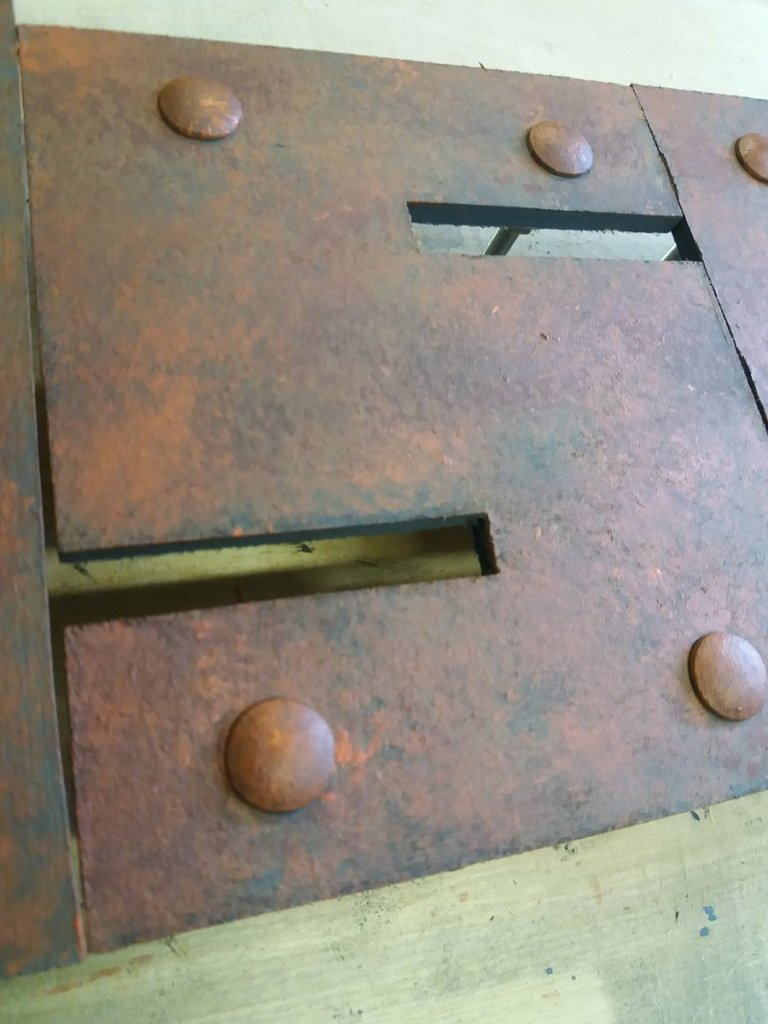 cut out letter painted to resemble rust with rivet heads
