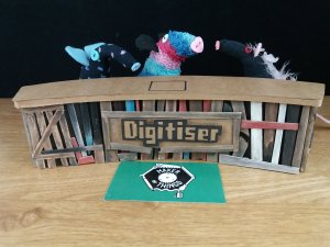 three sock creatures sit behind the model of the pallet wood version of the desk