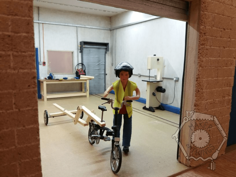Harriet is walking her Brompton bicycle out of her workshop shutters as seen from outside. Her bicycle is towing a trailer. The workshop interior is seen in the back ground.