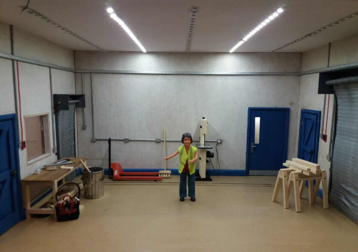 Harriet Board standing in the middle of her workshop. On the left is her tool bag and work bench, at the back is her pallet truck and band saw, on the right is a couple of saw horses and some four by two timber.